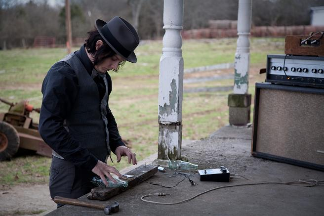 Jack White making a guitar out of a Coke bottle and some wood in the film It Might Get Loud